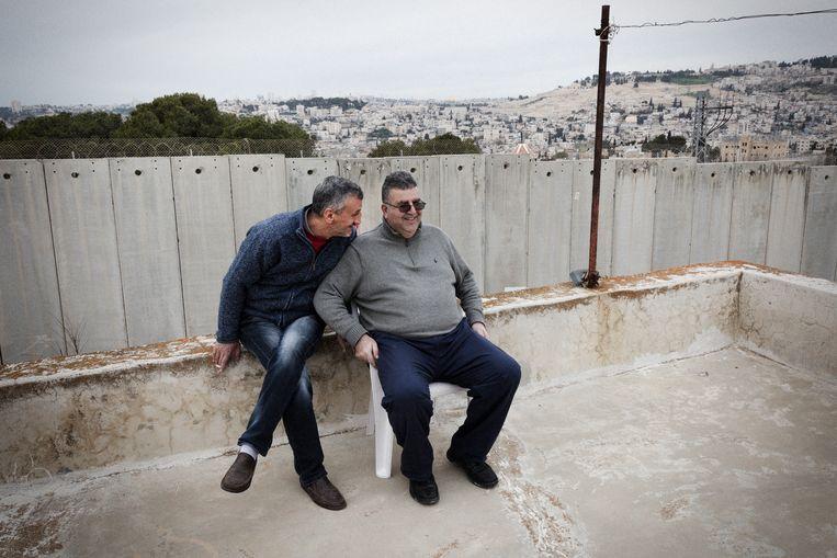 Burgemeester Ahmed Abu Hillal (rechts) met een jeugdvriend op diens dak. Vroeger speelden ze onder de bomen aan de andere kant van de muur, maar voor hun kinderen en kleinkinderen zijn die onbereikbaar.  Beeld Daniel Rosenthal