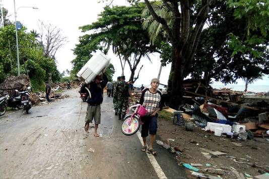 Inwoners verlaten hun beschadigde huizen in Carita.