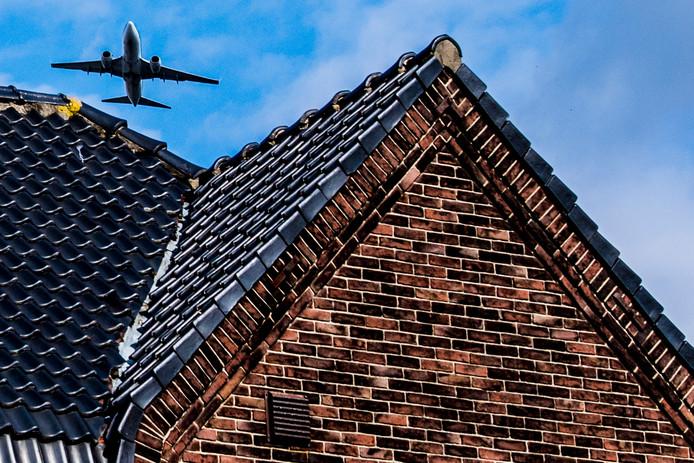 Een vliegtuig vliegt over een huis in de omgeving van Schiphol