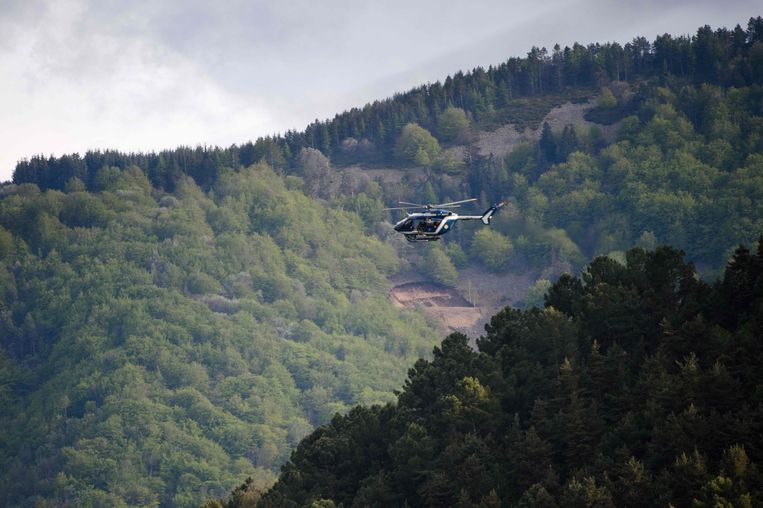 Een helikopter van de Franse politie hangt boven de heuvels van de Cevennen tijdens de jacht op een man die ervan wordt verdacht twee mensen te hebben doodgeschoten bij Les Plantiers in Zuid-Frankrijk. Beeld AFP