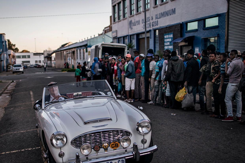In de rij voor voedseluitdeling in Johannesburg, Zuid-Afrika. Djaffar Shalchi: 'In de jaren tachtig werd het idee: laten we de rijken rijker maken. Daarvan profiteert ook de gewone man. Het is onzin gebleken.' Beeld AFP