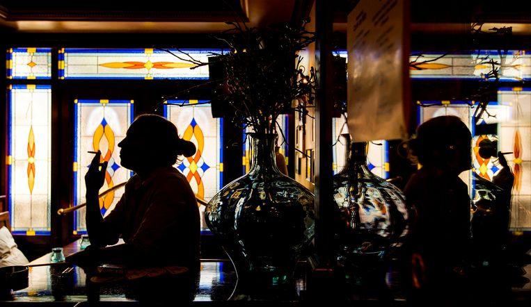 Rokers in de rookruimte van Café de Wit, waar de rookruimte zelf ook een café is. Beeld ANP