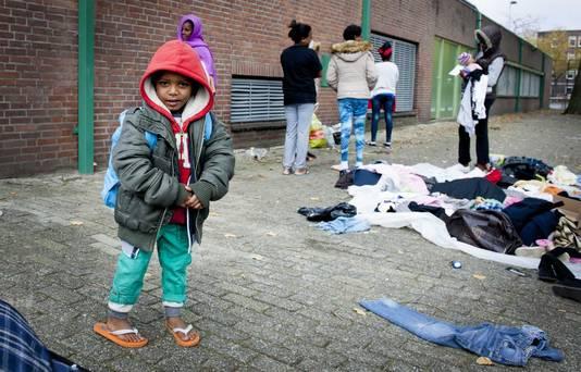 Vluchtelingen zoeken kleding uit die buurtbewoner hebben gebracht naast de Sportcentrum Schuttersveld, dat is ingericht als noodopvang.