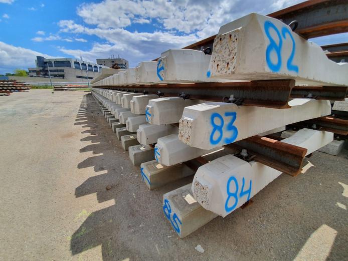 De betonnen dwarsliggers liggen genummerd klaar.