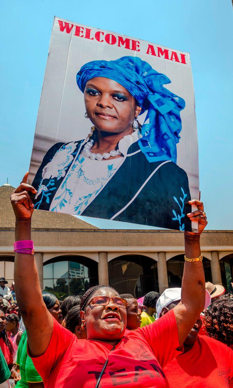 Een vrouw houdt een groot bord met de beeltenis van Grace Mugabe omhoog.
