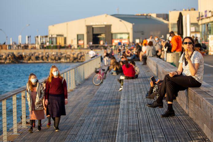 Mensen genieten van het zonnetje op de promenade in Tel Aviv.