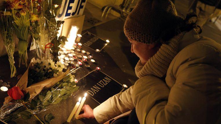 Bij de Deense ambassade in Parijs brandt een vrouw een een kaarsje voor de twee slachtoffers van de aanslag in Kopenhagen, dit weekend. Frankrijk werd zelf op 7 januari getroffen aanslagen die in totaal aan 17 mensen het leven kostten. Beeld ap