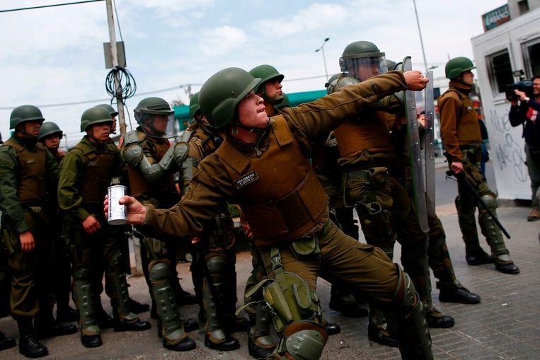 Een politieagent gooit traangas de menigte in in Santiago.