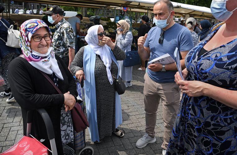 Maatschappelijk werker Zeki Celikkaya in de Rotterdamse wijk Delfshaven met twee Turkse zussen die zich wél hebben laten prikken. Beeld Marcel van den Bergh