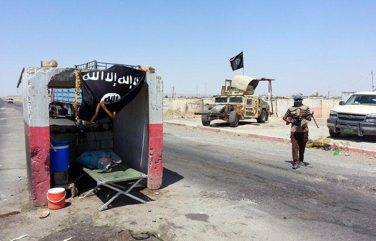 Een soennitische militant staat bij een checkpoint op de weg naar Baji in Noord-Irak. Beeld EPA