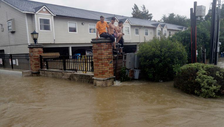 Bewoners van deels ondergelopen appartementen in Houston wachten op de omheining op hulp. Beeld ap