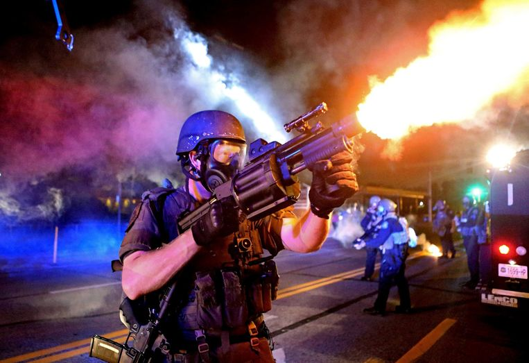 A member of the St. Louis County Police tactical team fires tear gas into a crowd of people in response to a series of gunshots fired at police during demonstrations in Ferguson, Missouri. Beeld REUTERS