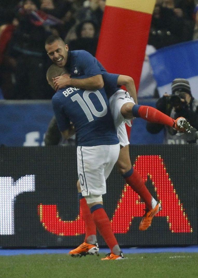 Benzema pakt Menez, goed voor de assist, op de schouder. Beeld REUTERS