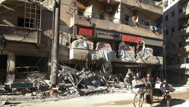 Paard en wagen rijdt langs het kapotgeschoten ziekenhuis al-Hakeem in het oosten van Aleppo. Beeld reuters