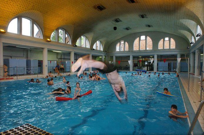 Een zwemmer neemt een duik in het Jan Guilinibad.