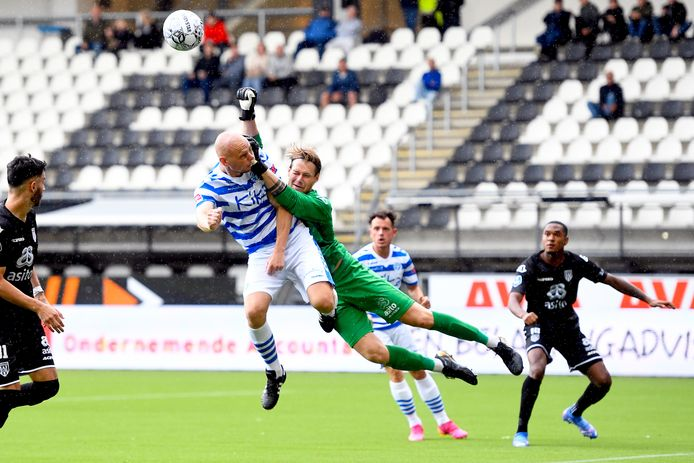 Heracles-proefkeeper Alessandro Damen bokst de bal weg voordat De Graafschap-voetballer Elmo Lieftink kan koppen.