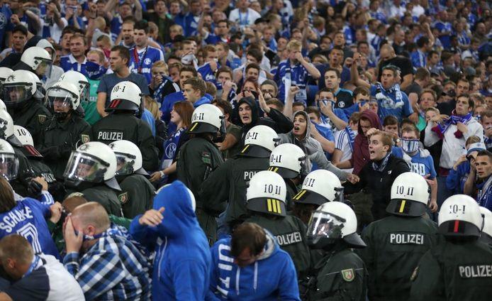 De ontevreden Schalke-supporters morren en dagen de politie uit.