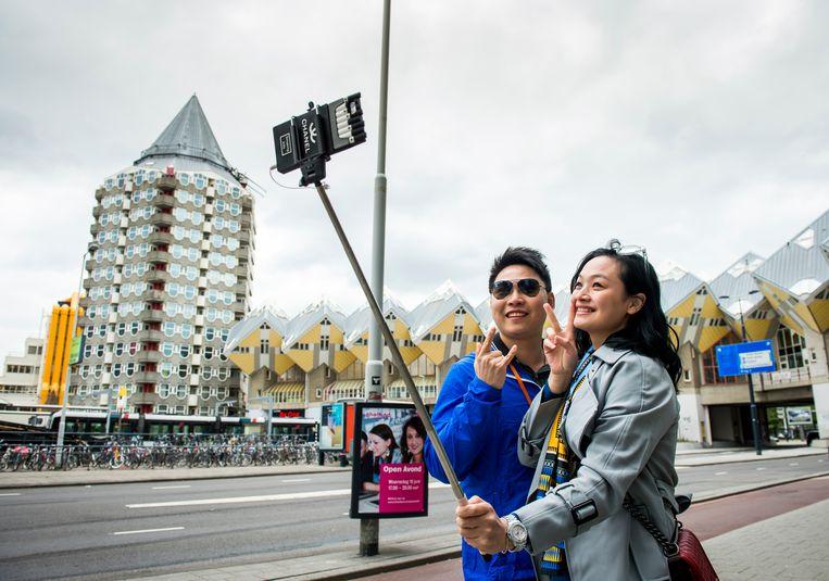 Voor de coronacrisis kwamen er tienduizenden Chinese toeristen naar Nederland. Op deze foto uit 2015 maken ze een selfie bij de kubuswoningen in Rotterdam. Beeld ANP, Marco de Swart