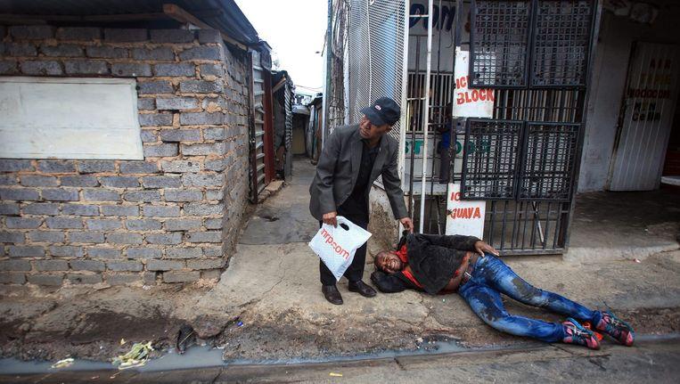 Een man ligt gewond op de grond nadat hij was aangevallen door bendes in de Alexandra Township in Johannesburg. De man zou in het ziekenhuis overlijden. Beeld epa
