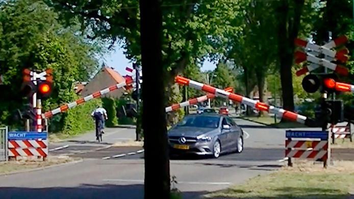 Levensgevaarlijke situaties: fietser en auto gaan op het laatste moment onder de spoorbomen door.