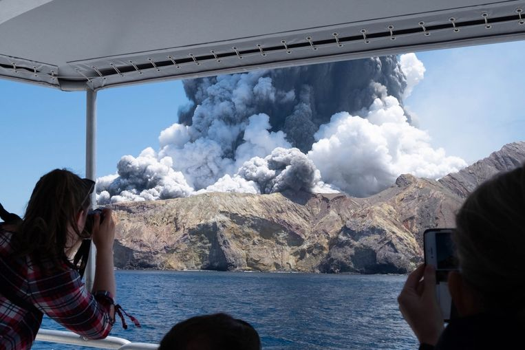 Toeristen die net van het eiland afkomen, maken vanaf de boot foto's van de uitbarsting.  Beeld EPA