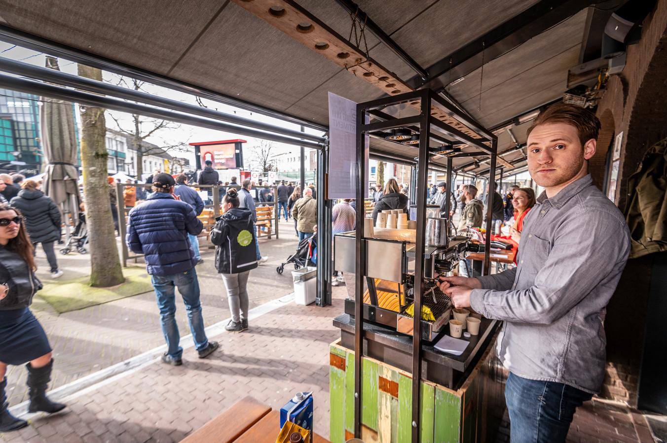 Nick Vink zaterdag achter zijn koffiebar bij H32 op de Heuvel. Op de achtergrond de vrijheidskaravaan van Thierry Baudet.