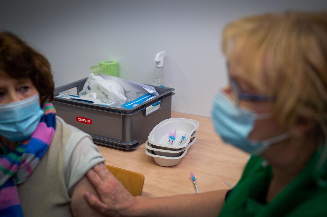 Vaccinatielocatie GGD Wijchen. De 83-jarige Door Plönes uit Nijmegen heeft zojuist haar eerste prik gezet.