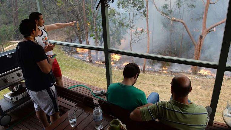 Inwoners van Faulconbridge, in de Blue Mountains, kijken vanaf de veranda naar een vuur dat dinsdag bewust is aangestoken om een corridor te creëren die grotere branden moet vermijden. Beeld afp