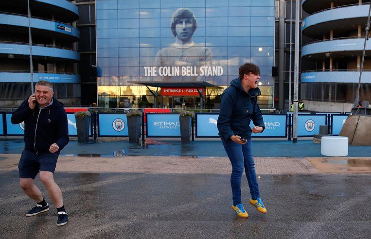 Fans van Manchester City vieren het kampioenschap van hun club buiten het Etihad Stadium. City speelde vandaag niet, maar werd kampioen dankzij verlies van Machester United. Beeld Action Images via Reuters