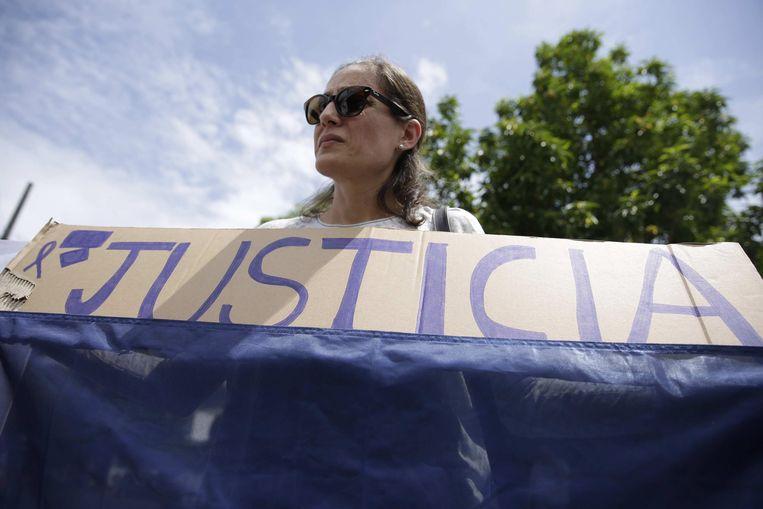 Een demonstrante houdt een spandoek omhoog met 'justicia' erop geschreven, gerechtigheid. Beeld EPA