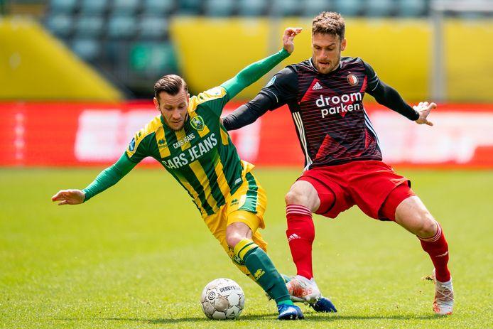 """John Goossens probeert overeind te blijven in duel met Feyenoorder Eric Botteghin. ,,Om de zege op Feyenoord aan mij op te hangen, is niet terecht."""""""