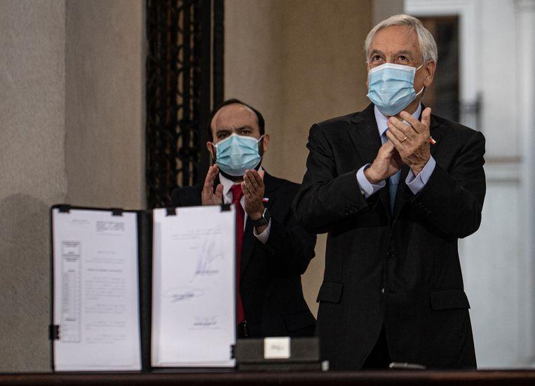 De Chileense president Sebastian Pinera (rechts) bij het ondertekenen van de wettekst. De stemming zal nu plaatsvinden op 15 en 16 mei. Beeld AP