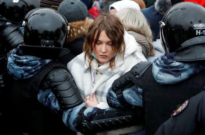 Een jonge vrouw wordt door de politie tegengehouden bij het protest in Moskou.