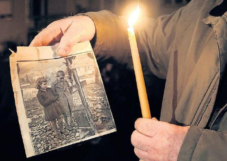 Een overlevende van het bloedbad in Distomo houdt, tijdens een protest, een foto vast van zichzelf en zijn zus bij het graf van zijn ouders. Beeld EPA