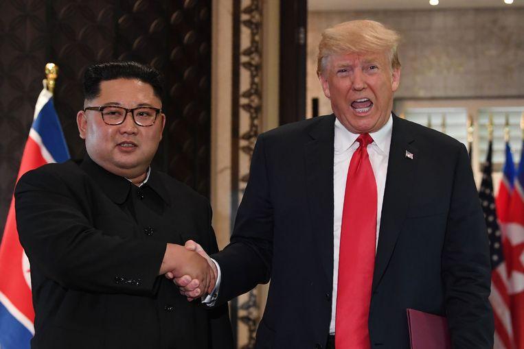 Donald Trump en Kim Jong-un schudden elkaar de hand tijdens hun ontmoeting in Singapore. Beeld AFP