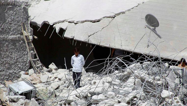 Een man in Idlib, Syrië, tussen de puinhopen van een gebouw dat door Amerikaanse bommen is geraakt. Beeld reuters