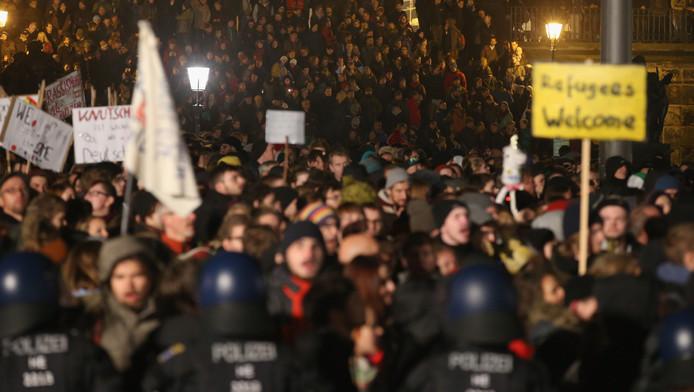 Demonstranten staan achter de politie te schreeuwen richting Pegida-supporters, die zich verzamelen voor de mars ter ere van de eerste verjaardag van de beweging.