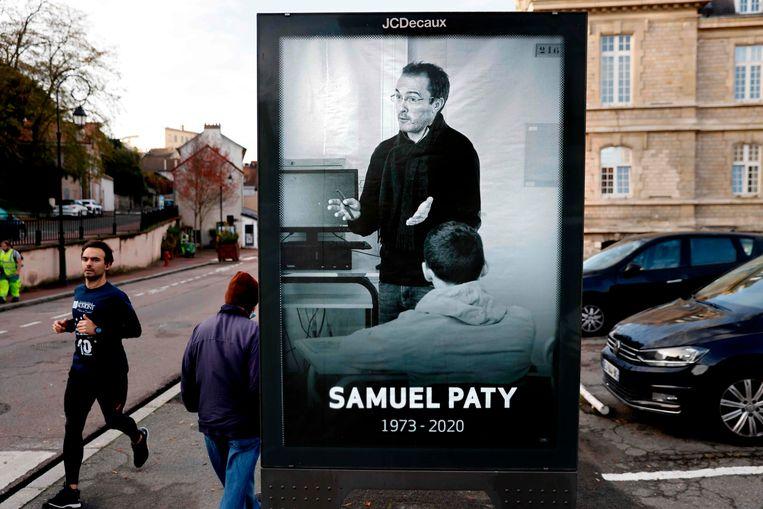 Voetgangers passeren een poster met daarop de vermoorde Franse leraar Samuel Paty. Beeld AFP