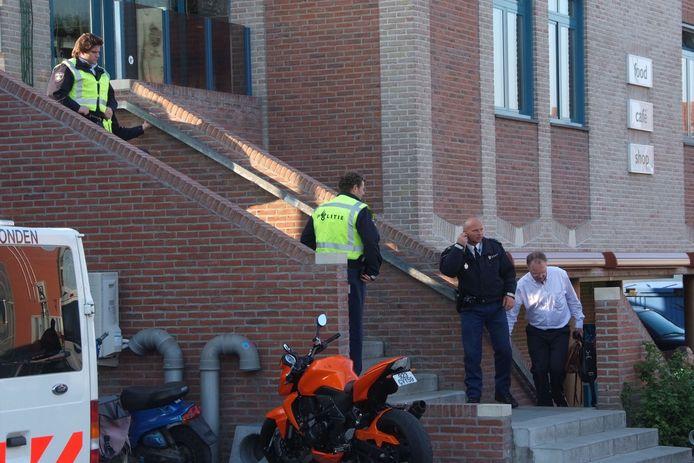 Voor de tweede keer in een jaar een inval bij Checkpoint. Een man in burger komt met 2 tassen uit het pand.