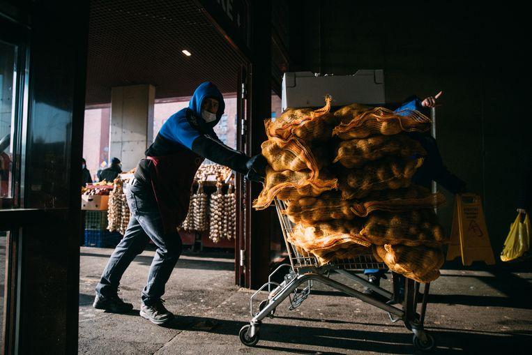 Een man brengt aardappelen naar het gesloten gedeelte van de markt. Beeld Marlena Waldthausen