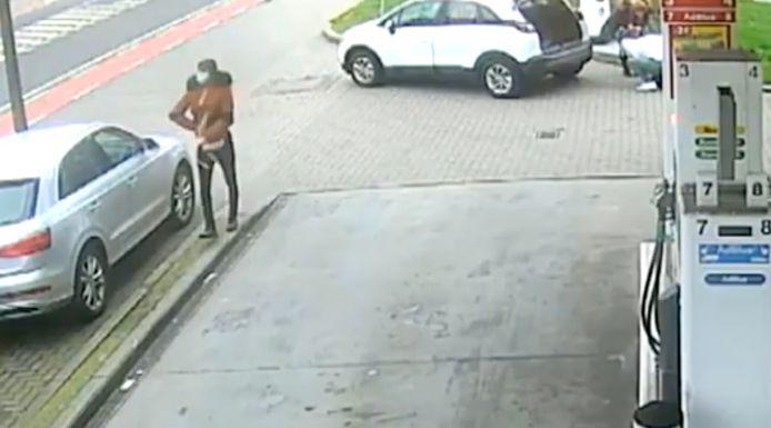 De verdachte steekt de gestolen handtas onder zijn jas. De broer en zus bevinden zich op dat moment nog achter de auto (rechts) en hebben niks in de gaten.