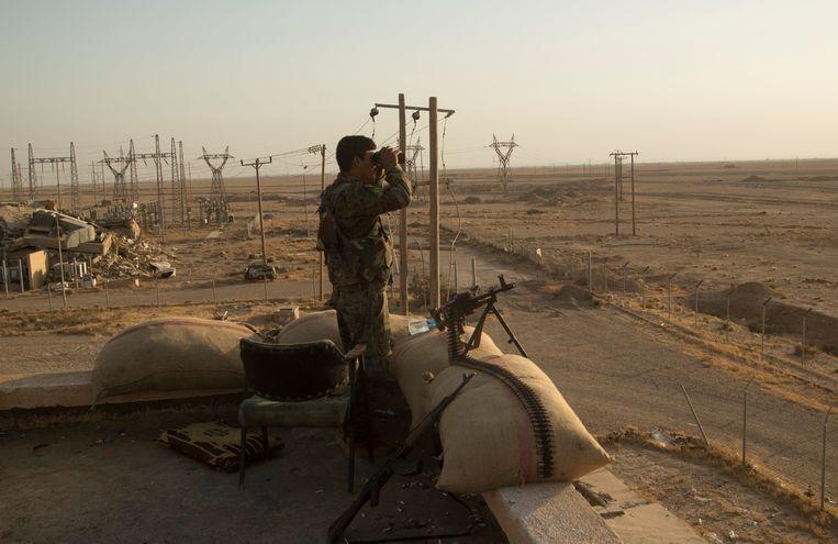 Een soldaat van de Syrische Democratische Strijdkrachten kijkt uit over de woestijn in het oosten van Syrië Beeld Photo News