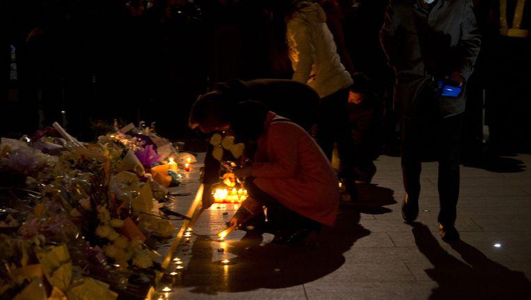 Inwoners van Shanghai plaatsen bloemen en kaarsen bij de plek waar op oudejaarsnacht 36 mensen omkwamen. Beeld ap