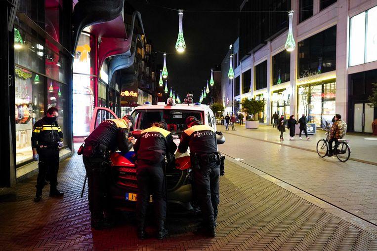 Politie houdt een oogje in het zeil in de Grote Marktstraat. Jongeren hebben via sociale media opgeroepen om te rellen in het centrum van de Hofstad.  Beeld ANP