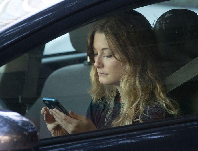 Een jonge vrouw kijkt op haar smartphone terwijl ze achter het  stuur zit.
