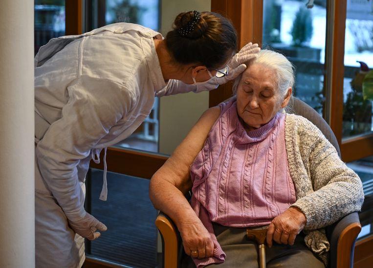 De 84-jarige Siegrid Becsei krijgt in Brandenburg (Duitsland) het coronavaccin toegediend. Beeld