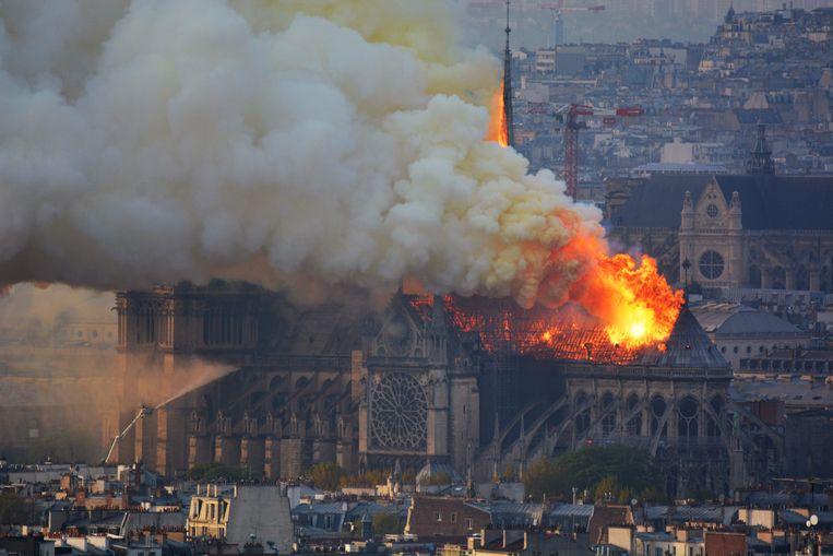 Rook en vlammen stijgen op uit de Notre Dame Kathedraal. Beeld AFP