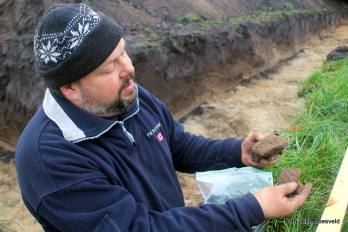 Archeoloog Eric van der Kuijl laat de bodem en een scherf van een Kalenderberg-urn zien uit 800 voor Christus