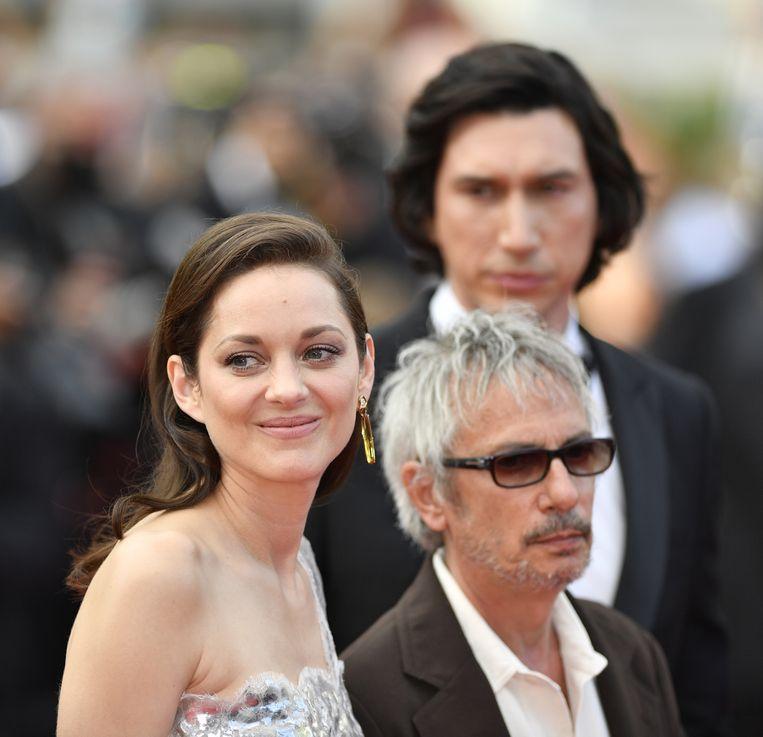 Marion Cotillard en regisseur Leos Carax op de rode loper bij de première van Annette, op de 74ste editie van het filmfestival van Cannes. Beeld Getty