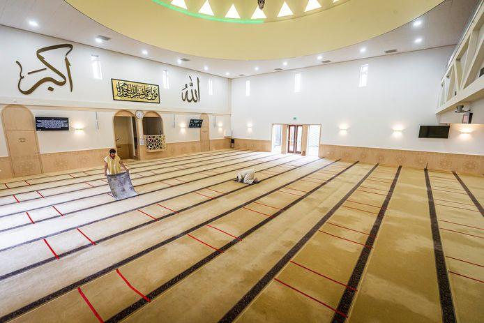 Op de vloer in de Dordtse El Fath Moskee zijn ruimten afgeplakt voor de gebedskleden. Zo kan het offerfeest toch doorgaan.